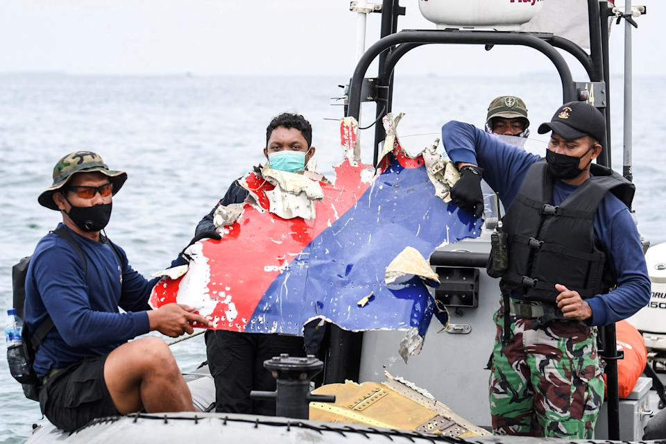 Indonesian Navy personnel carry debris believed to be from the Sriwijaya Air SJ-182 plane, which crashed into the sea, off the Jakarta coast.