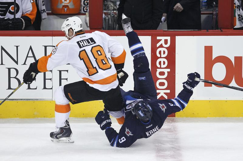 Winnipeg Jets' Evander Kane (9) is dumped by Philadelphia Flyers' Adam Hall (18) during first-period NHL hockey game action in Winnipeg , Manitoba, Friday, Nov. 15, 2013. (AP Photo/The Canadian Press, John Woods)