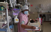 A nurse attends to a newborn baby in the intensive care unit of the Women's Hospital maternity ward in La Paz, Bolivia, Thursday, Aug. 13, 2020. Doctors say the supply of oxygen for the babies is becoming scarce, the result of nationwide blockades by supporters of the party of former President Evo Morales who object to the recent postponement of elections. Bolivia's political and social crisis is coinciding with the continued spread of the new coronavirus. (AP Photo/Juan Karita)