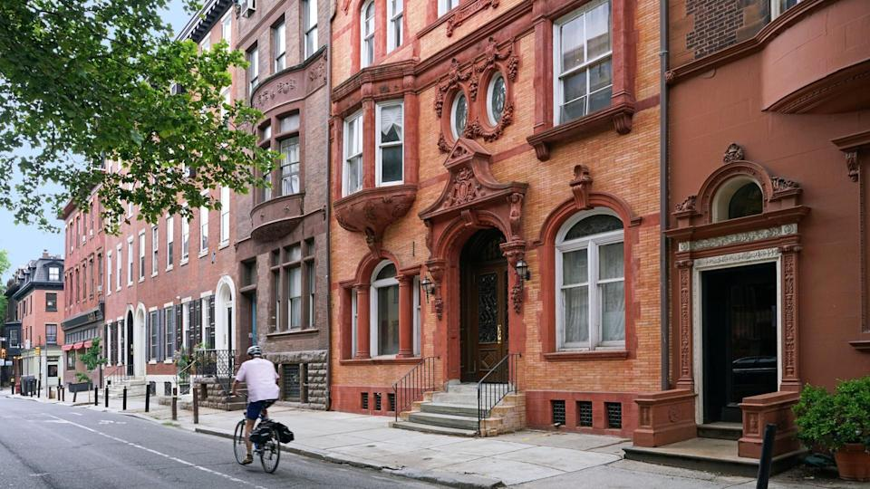 urban street with elegant old brownstone style townhouses or apartment buildings.