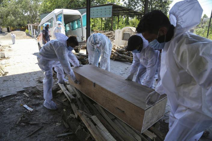 Health workers and relatives carry the body of a COVID-19 victim for cremation in Jammu, India, Monday, May 24, 2021. India crossed another grim milestone Monday of more than 300,000 people lost to the coronavirus as a devastating surge of infections appeared to be easing in big cities but was swamping the poorer countryside. (AP Photo/Channi Anand)