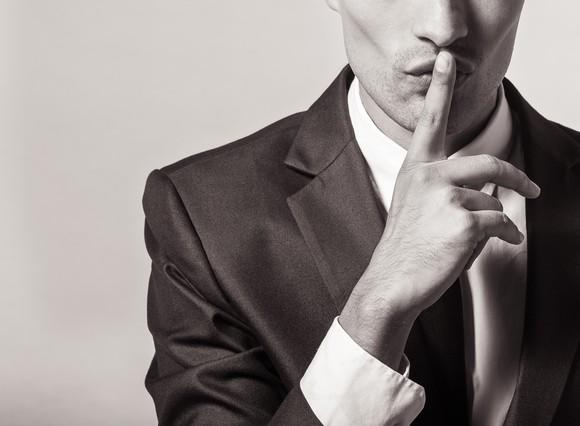 A man holding a finger to his lips to make a shushing sound.