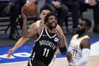 Brooklyn Nets guard Kyrie Irving (11) drives to the basket for a shot past Dallas Mavericks guard Josh Green, rear, and Tim Hardaway Jr., right, in the second half of an NBA basketball game in Dallas, Thursday, May 6, 2021. (AP Photo/Tony Gutierrez)