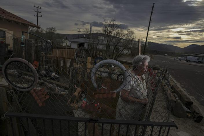 A woman stands inside a fenced yard on a rural street