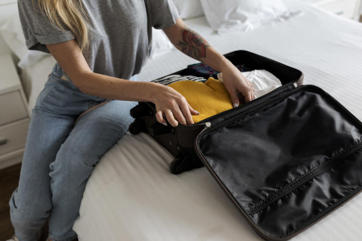 Are you guilty of putting your suitcase on the bed? [Photo: Getty]