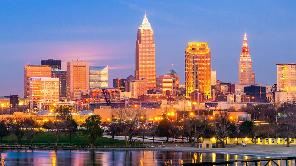 Downtown Cleveland, Ohio, glows in setting sunlight as the full moon prepares to rise under the pink clouds at center left.