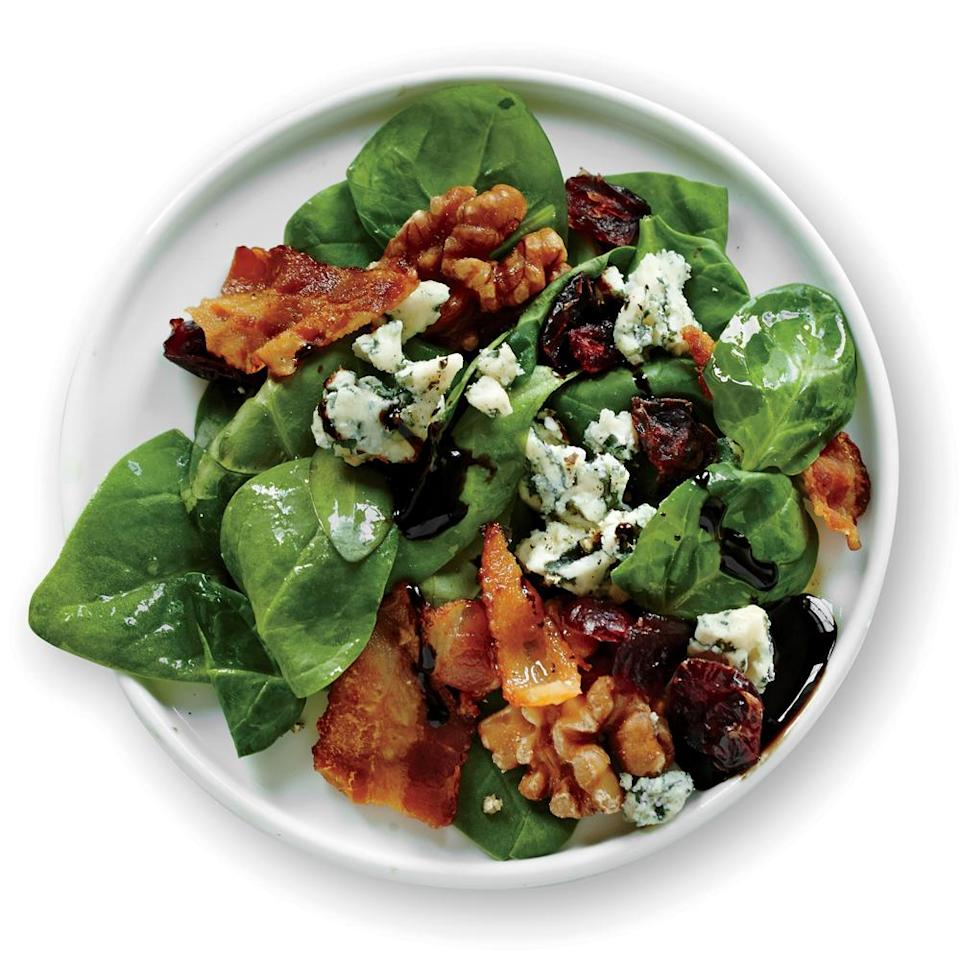 """<p>This <a href=""""https://www.myrecipes.com/salad-recipes"""" rel=""""nofollow noopener"""" target=""""_blank"""" data-ylk=""""slk:easy salad"""" class=""""link rapid-noclick-resp"""">easy salad</a> features bagged baby spinach paired with a homemade vinaigrette, dried cranberries, toasted walnuts, crumbled bacon, and blue cheese. </p>"""