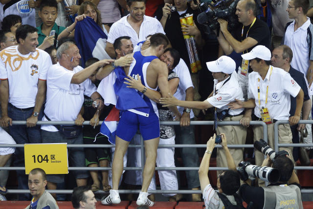 France's Steeve Guenot celebrates with fans after his gold medal match in the 66-kilogram greco-roman wrestling competition at the Beijing 2008 Olympics in Beijing Wednesday, Aug. 13, 2008. (AP Photo/Ed Wray)