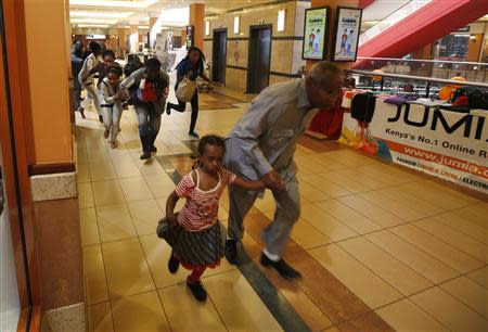 People with children run for safety as armed police hunt gunmen who went on a shooting spree at Westgate shopping centre in Nairobi, September 21, 2013. REUTERS/Goran Tomasevic