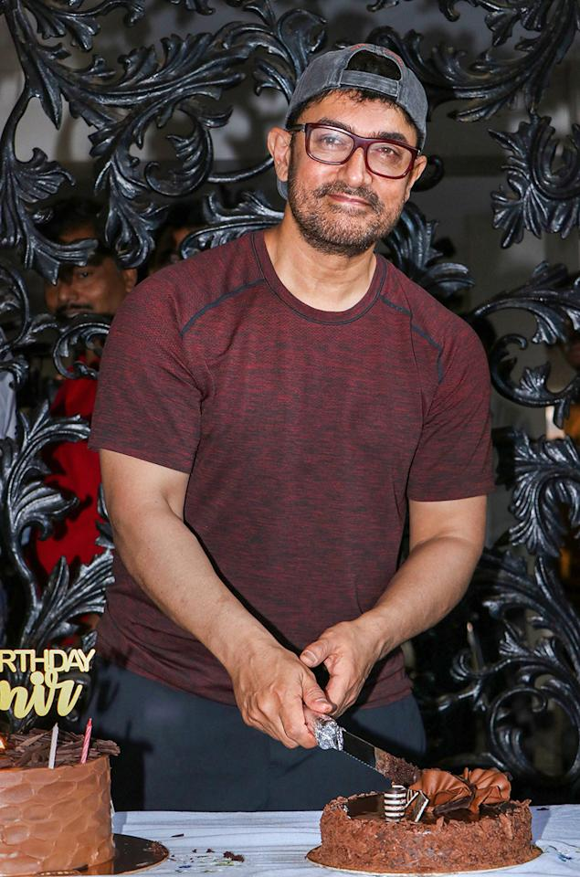 Bollywood actor Aamir Khan cuts a cake during his 54th birthday celebration at his residence, in Mumbai. (Image: PTI)