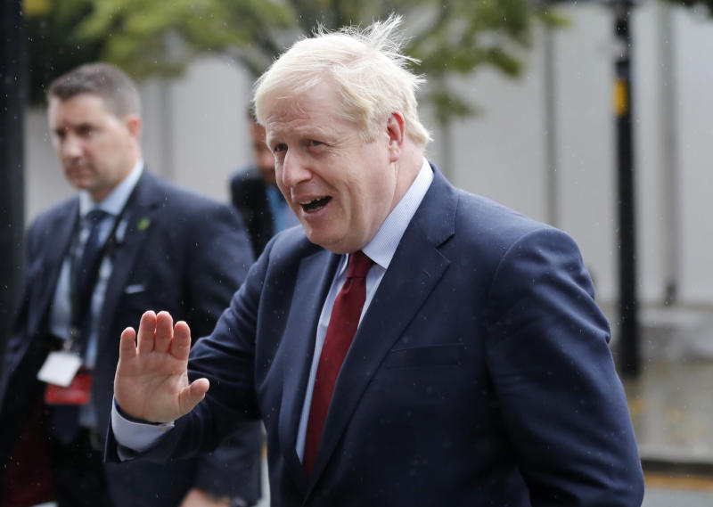 Britain's Prime Minister Boris Johnson rushes through the rain during the Conservative Party Conference in Manchester, England, Tuesday, Oct. 1, 2019. Boris Johnson said Tuesday that his government prepared at last to make firm proposals for a new divorce deal with the European Union. Britain is due to leave the 28-nation bloc at the end of this month, and EU leaders are growing impatient with the U.K.'s failure to set out detailed plans for maintaining an open border between Northern Ireland and Ireland — the key sticking point to a deal. (AP Photo/Frank Augstein)