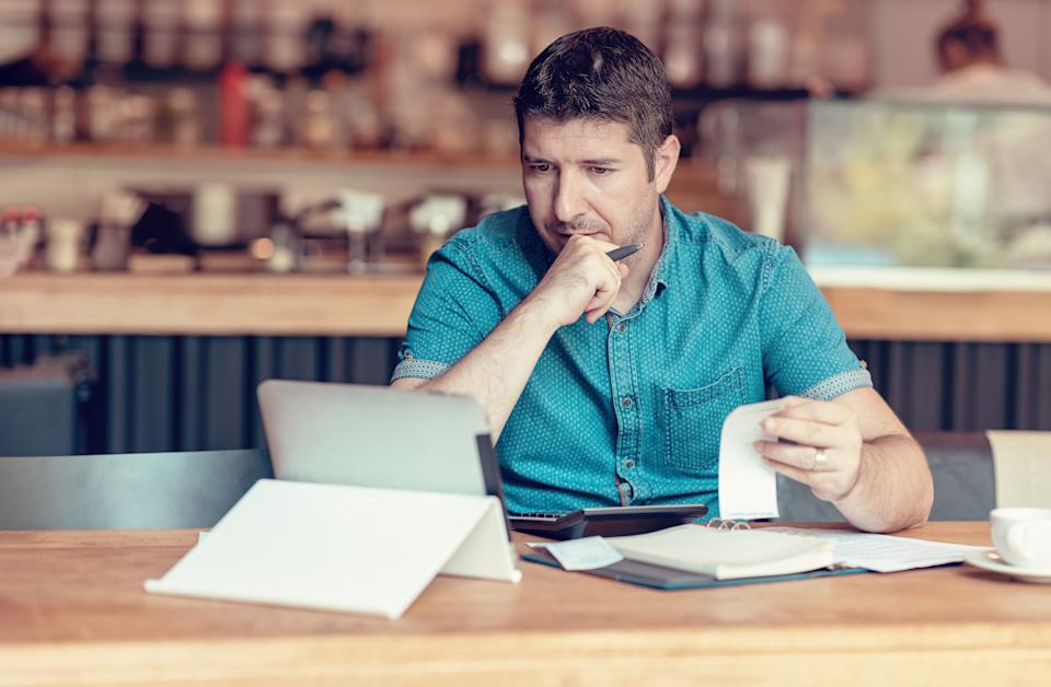 Restaurant owner checking monthly reports on a tablet, bills and expenses of his small business