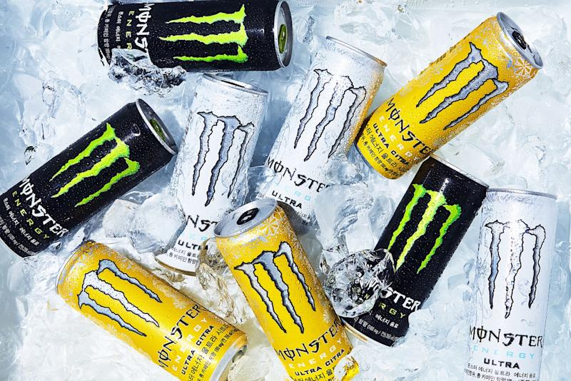 Black, white, and yellow Monster Energy cans on ice.