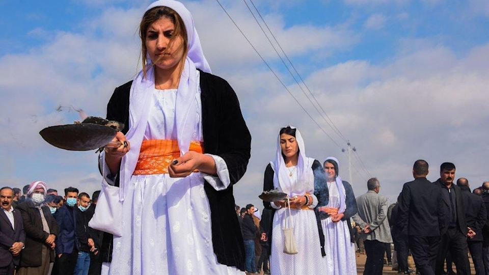 Women burn incense during a procession at the mass funeral in Kocho on 6 February 2021