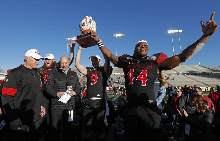 San Diego State linebacker Kyahva Tezino (44), quarterback Ryan Agnew (9), tight end Parker Houston, second from left, and coach Rocky Long, left, celebrate with the trophy after their team beat Central Michigan in the New Mexico Bowl NCAA college football game on Saturday, Dec. 21, 2019 in Albuquerque, N.M. (AP Photo/Andres Leighton)