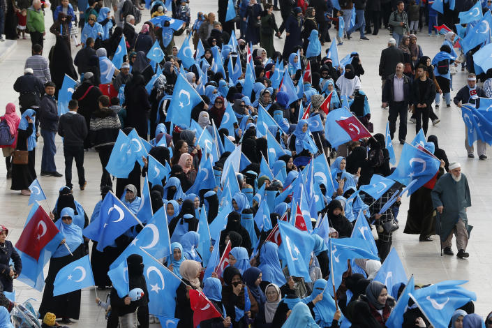 FILE - In this file photo dated Tuesday, Nov. 6, 2018, people from the Uighur community living in Turkey carry flags of what ethnic Uighurs call 'East Turkestan', during a protest in Istanbul, against what they allege is oppression by the Chinese government to Muslim Uighurs in far-western Xinjiang province. The prominent British human rights lawyer Geoffrey Nice is convening an independent tribunal in London with public hearings in 2021, to look into the Chinese government's alleged rights abuses against the Uighur Muslim minority in the far western province of Xinjiang. (AP Photo/Lefteris Pitarakis, FILE)
