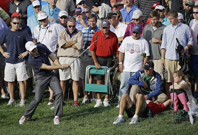 United States' Keegan Bradley hits his second shot on the 14th hole during a four-ball match at the Presidents Cup golf tournament at Muirfield Village Golf Club on Thursday, Oct. 3, 2013, in Dublin, Ohio. Bradley's first shot on the hole hit the man lying on the ground at right. Bradley and Phil Mickelson lost 2 and 1 to the International team's Louis Oosthuizen and Charl Schwartzel. (AP Photo/Darron Cummings)