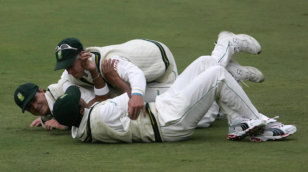 CENTURION, SOUTH AFRICA:  South Africa's team members miess around as they wait to see if the game will go on after being stopped due to bad light during New Zealand's 2nd innings.In the picture is AB de Villiers (top) of Makhaya Ntini and Dale Steyn.  South Africa ened its 2nd innings with a lead of 249 runs on the 4th day of the First Cricket Test 18 April 2006 between New Zealand and South Africa at  SuperSport Park, Centurion. South  AFP PHOTO / ALEXANDER JOE   ,  (Photo credit should read ALEXANDER JOE/AFP/Getty Images)