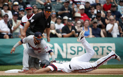 Minnesota Twins third baseman Marvin Gonzalez (9) tags out Chicago White Sox's Jose Rondon, bottom, as umpire Sam Holbrook (34) watches during the second inning of a baseball game Sunday, June 30, 2019, in Chicago. (AP Photo/Jeff Haynes)