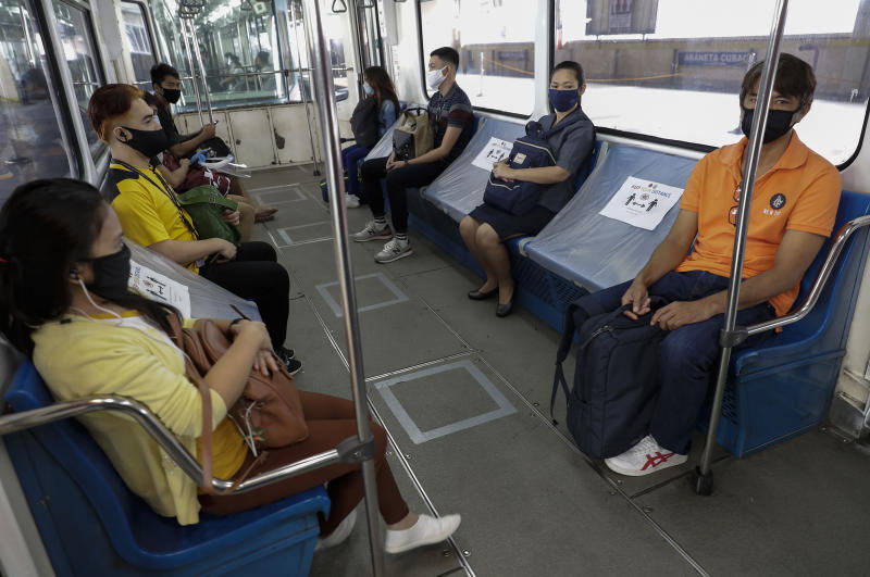 People ride a train with seats arranged for social distancing measures during the first day of a more relaxed coronavirus lockdown in Manila, Philippines on Monday, June 1, 2020. Traffic jams and crowds of commuters are back in the Philippine capital, which shifted to a more relaxed quarantine with limited public transport in a high-stakes gamble to slowly reopen the economy while fighting the coronavirus outbreak. (AP Photo/Aaron Favila)