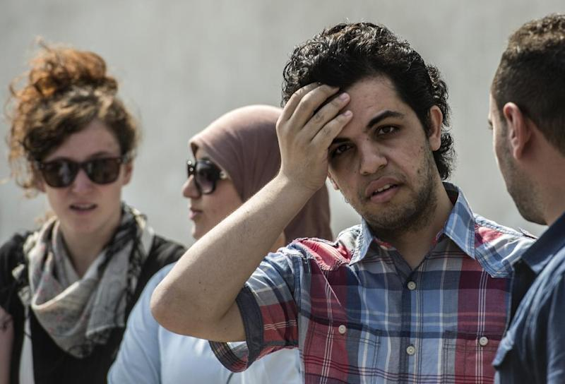 Newly freed Al-Jazeera news channel's journalist Abdullah Elshamy (2nd R) stands outside the court during the trial of three of his colleagues for allegedly supporting the Muslim Brotherhood on June 23, 2014