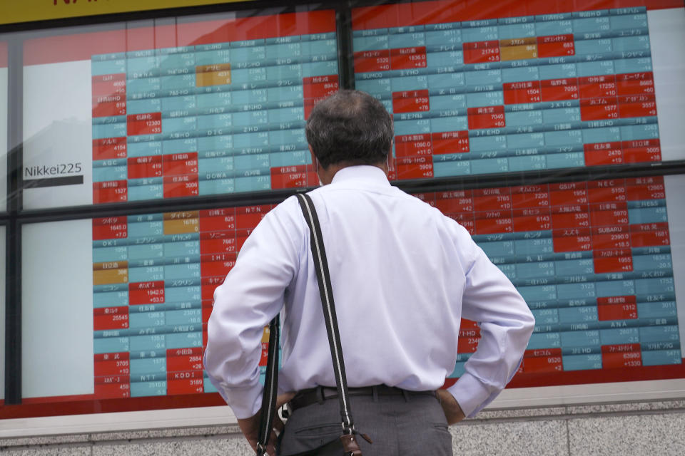 A man looks at an electronic stock board showing Japan's Nikkei 225 index at a securities firm in Tokyo Wednesday, June 24, 2020. Asian shares were mostly higher on Wednesday with another mood boost from Wall Street, but fears persist over the surge in coronavirus cases in parts of the world. (AP Photo/Eugene Hoshiko)