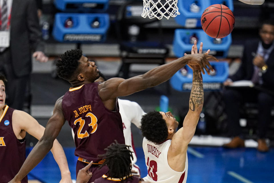 Iona forward Nelly Junior Joseph (23) blocks the shot of Alabama guard Jahvon Quinerly (13) in the first half of a first-round game in the NCAA men's college basketball tournament at Hinkle Fieldhouse in Indianapolis, Saturday, March 20, 2021. (AP Photo/Michael Conroy)