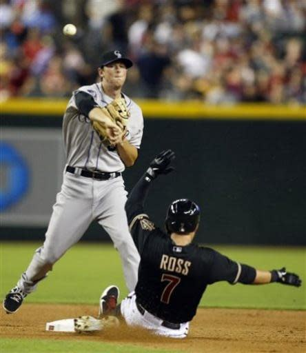 Colorado Rockies second baseman DJ LeMahie, left, turns the double play while avoiding Arizona Diamondbacks Cody Ross, right, in the fifth inning during a baseball game on Friday, July 5, 2013, in Phoenix. (AP Photo/Rick Scuteri)