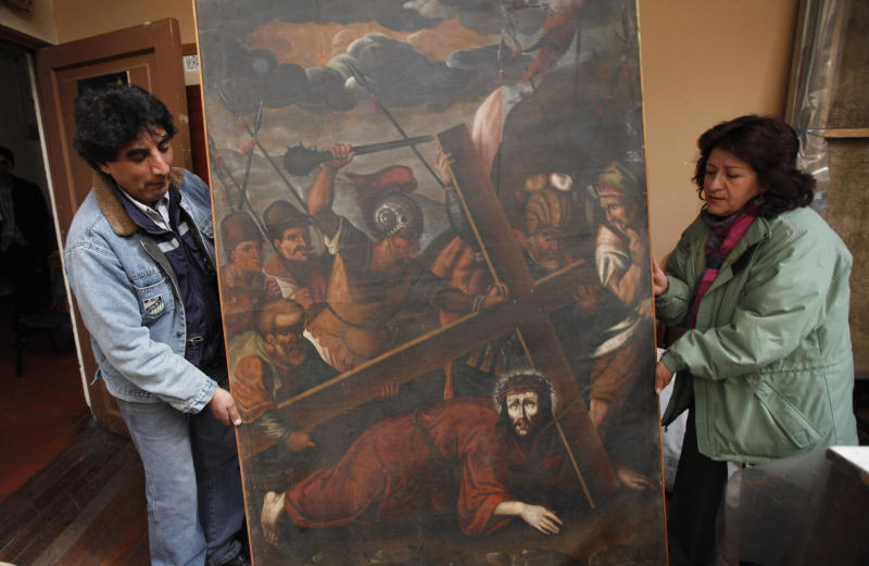 "In this Aug. 21, 2013 file photo, workers from the Culture Ministry display a recovered 18th century painting by an anonymous artist depicting Jesus in La Paz, Bolivia. This painting titled ""Jesus con la Cruz a Cuesta"" was stolen from the San Pedro de la Paz church in Bolivia on June 11, 2003, and recovered in the Peruvian capital of Lima in April 2005. Increasingly bold thefts plague colonial churches in remote Andean towns in Bolivia and Peru, where religious and civil authorities say cultural treasures are disappearing at an alarming rate. (AP Photo/Juan Karita)"