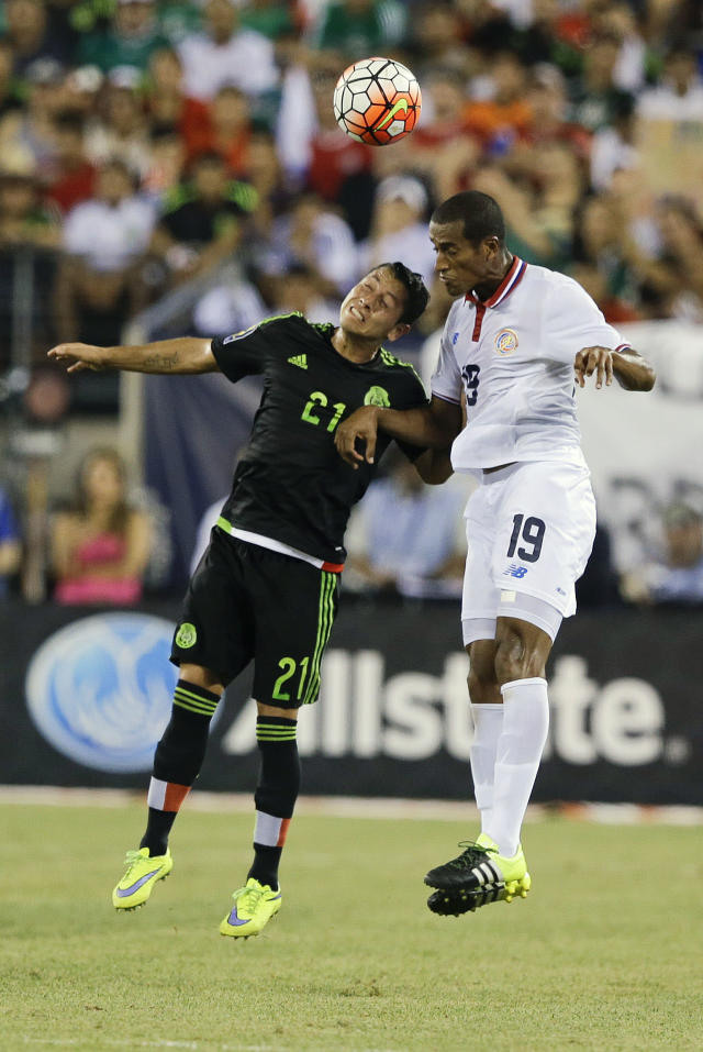 Mexico's Carlos Esquivel (21) and Costa Rica's Roy Miller (19) fight for the ball during the overtime period of a CONCACAF Gold Cup soccer match Sunday, July 19, 2015, at MetLife stadium in East Rutherford, N.J. (AP Photo/Mel Evans)