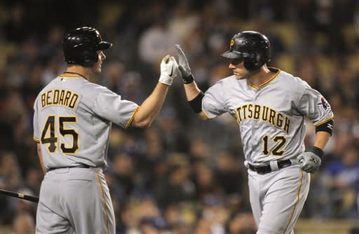 Pittsburgh Pirates' Clint Barmes, right, is congratulated by teammate Erik Bedard after hitting a solo home run during the third inning of their baseball game against the Los Angeles Dodgers, Wednesday, April 11, 2012, in Los Angeles. (AP Photo/Mark J. Terrill)