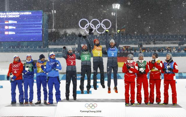 Nordic Combined Events - Pyeongchang 2018 Winter Olympics - Men's Team 4 x 5 km Final - Alpensia Cross-Country Skiing Centre - Pyeongchang, South Korea - February 22, 2018 - Gold medallists Vinzenz Geiger, Fabian Riessle, Eric Frenzel and Johannes Rydzek of Germany celebrate next to silver medallists Norway and bronze medallists Austria during the victory ceremony. REUTERS/Kai Pfaffenbach
