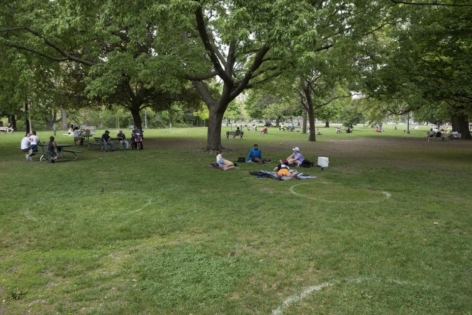 People sit amid unoccupied physical distancing circles at a park