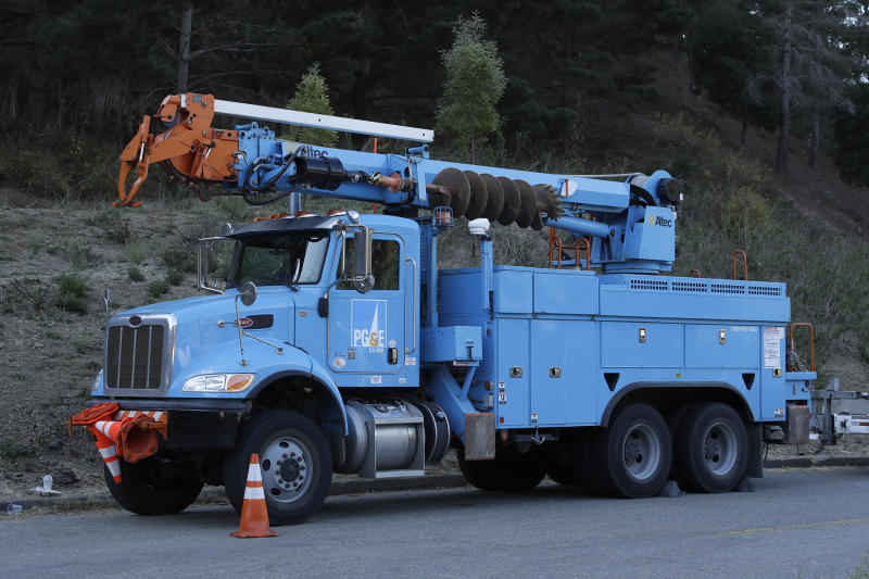 PG & E maintenance truck waits near the Caldecott Tunnel on Wednesday, Oct. 9, 2019, in Oakland, Calif. Pacific Gas & Electric has cut power to more than half a million customers in Northern California hoping to prevent wildfires during dry, windy weather throughout the region. (AP Photo/Ben Margot)