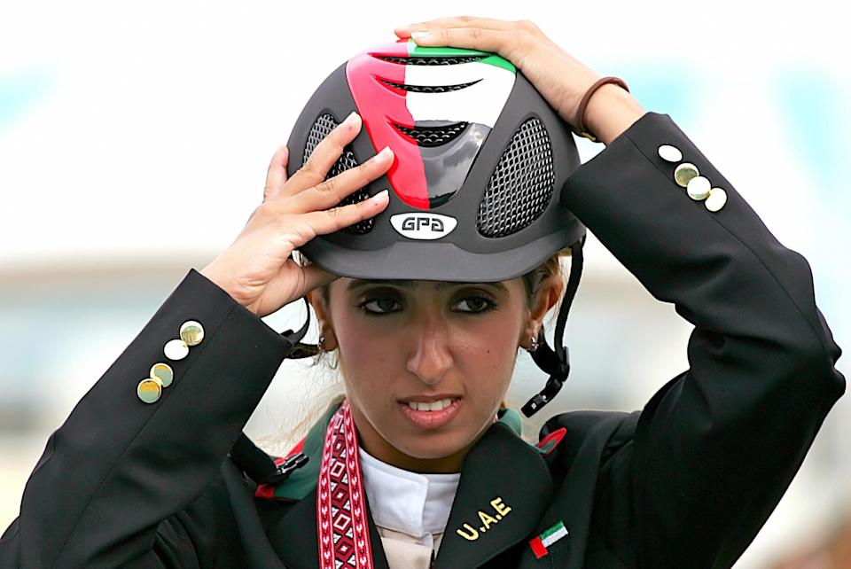 Doha, QATAR:  Sheikha Latifa al-Maktum of the United Arab Emirates stands on the winners' podium after winning the bronze medal in the final of the countries' equestrian teams at the Doha equestrian club at the 15th Asian Games in Doha, 11 December 2006.  Saudi Arabia clinched the gold and South Korea won the silver. AFP PHOTP/MARWAN NAAMANI  (Photo credit should read MARWAN NAAMANI/AFP via Getty Images)