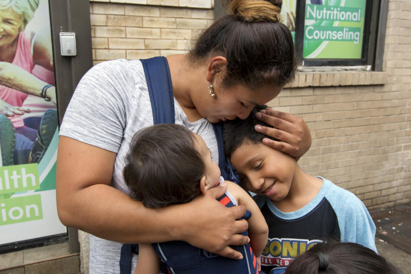 FILE - In this Friday, Aug. 3, 2018 file photo, Honduran Eilyn Carbajal hugs her then-8-year-old son Nahun Eduardo Puerto Pineda, right, after they were reunited at the Cayuga Center, in New York. Fearful immigrant families hoping to reunite with children and teenagers who crossed the border alone are facing an intimidating system that includes submitting fingerprints by all adults in the household where a migrant child will live. Under new rules, the finger prints are shared with Immigration and Customs Enforcement. (AP Photo/Richard Drew)