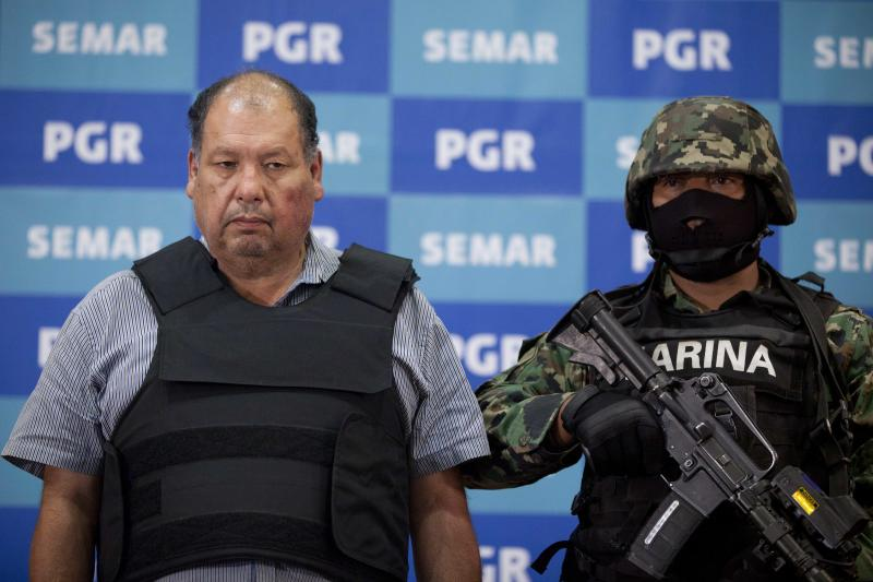 """A Mexican Navy officer stands next to Mario Cardenas Guillen, also known as """"El Gordo"""" and """"M-1,"""" during his presentation to the media in Mexico City, Tuesday, Sept. 4, 2012. Authorities says Cardenas Guillen, a top leader of the Gulf drug cartel, is the brother of Osiel Cardenas Guillen, who led the cartel until he was detained in 2003. Osiel Cardenas was extradited in 2007 to the United States and sentenced to 25 years in prison. (AP Photo/Alexandre Meneghini)"""