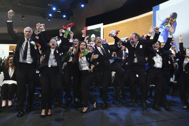 Italy's National Olympic Committee (CONI) president Giovanni Malago, left, and members of Milan-Cortina delegation celebrate after winning the bid to host the 2026 Winter Olympic Games, during the first day of the 134th Session of the International Olympic Committee (IOC), at the SwissTech Convention Centre, in Lausanne, Switzerland, Monday, June 24, 2019. Italy will host the 2026 Olympics in Milan and Cortina d'Ampezzo, taking the Winter Games to the Alpine country for the second time in 20 years. (Philippe Lopez/Pool via AP)