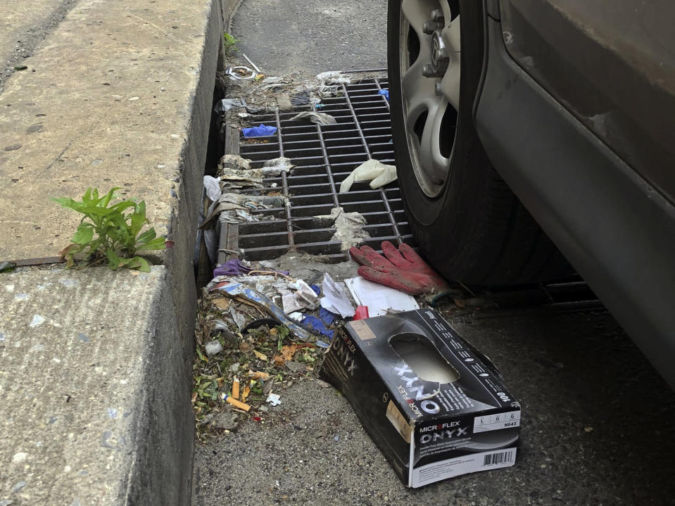 This Friday, May 22, 2020 photo shows a discarded glove on a storm drain in Philadelphia. Between mid-March, when the city's stay-at-home order was issued, and the end of April, most of the 19 sewer and storm water pumping stations in Philadelphia had experienced clogs from face masks, gloves and wipes residents had pitched into the potty, Philadelphia Mayor Jim Kenney said. (AP Photo/Jonathan Poet)