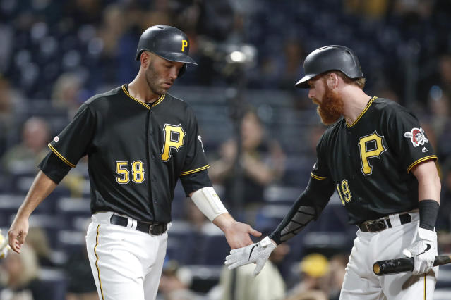 Pittsburgh Pirates' Jacob Stallings, left, is greeted by Colin Moran after scoring against the Miami Marlins on a triple by Adam Frazier during the fourth inning of a baseball game Wednesday, Sept. 4, 2019, in Pittsburgh. (AP Photo/Keith Srakocic)