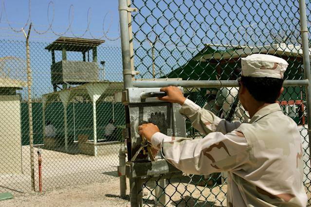 In this photo reviewed by US military officials, a guard opens a gate while in the background two detainees sit in a rest area behind fencing, within the grounds of Camp Delta 4 military-run prison, at the Guantanamo Bay U.S. Naval Base, Cuba June 27, 2006. The U.S. Supreme Court is preparing a potential landmark ruling that could determine the fate of the military tribunals created by President George W. Bush to try Guantanamo prisoners for war crimes. The ruling by the nation's highest court, which is expected later this week, will be one of the most significant presidential war powers cases since World War Two and could determine whether the tribunals are lawful. REUTERS/Brennan Linsley/Pool