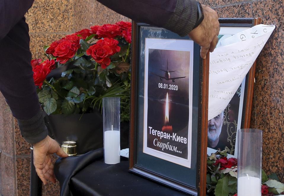 """A man places a memorial poster showing a Ukrainian 737-800 plane that crashed on the outskirts of Tehran, Iran, and and a candle, the words reading """"Tehran - Kyiv, we're mourning"""" outside the Iranian Embassy in Kyiv, Ukraine, Wednesday, Jan. 8, 2020. A Ukrainian airplane carrying 176 people crashed on Wednesday shortly after takeoff from Tehran's main airport, killing all onboard, Iranian state TV and officials in Ukraine said. The portrait of Iranian Revolutionary Guard Gen. Qassem Soleimani killed by U.S. airstrike in Iraq is seen behind. (AP Photo/Efrem Lukatsky)"""