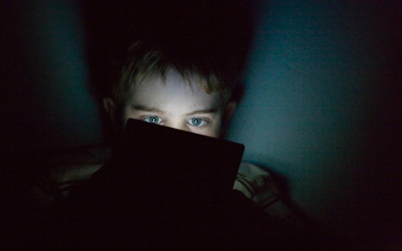 A young boy plays a portable games console at night - Credit: Christina Kennedy/Alamy Stock Photo