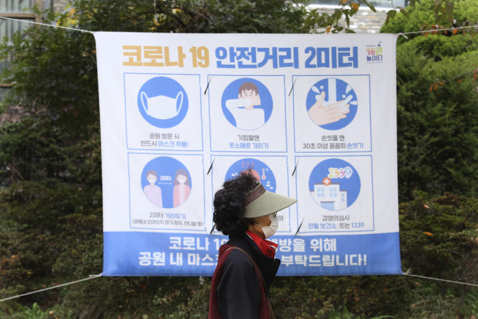 """A woman wearing a face mask to help curb the spread of the coronavirus walks by a social distancing sign at a park in Seoul, South Korea, Friday, Oct. 16, 2020. South Korea's daily coronavirus tally has dropped below 50 for the first time in more than two weeks despite reports of small-scale local infections. The sign reads: """"Corona 19, safety distance 2 meters."""" (AP Photo/Ahn Young-joon)"""