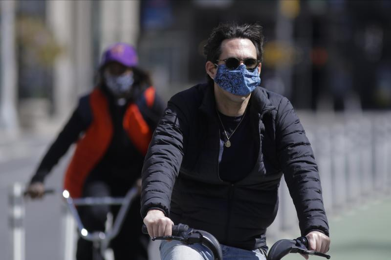 Cyclists wear protective masks as they pass Madison Square Park, Tuesday, May 12, 2020, in New York. (AP Photo/Frank Franklin II)