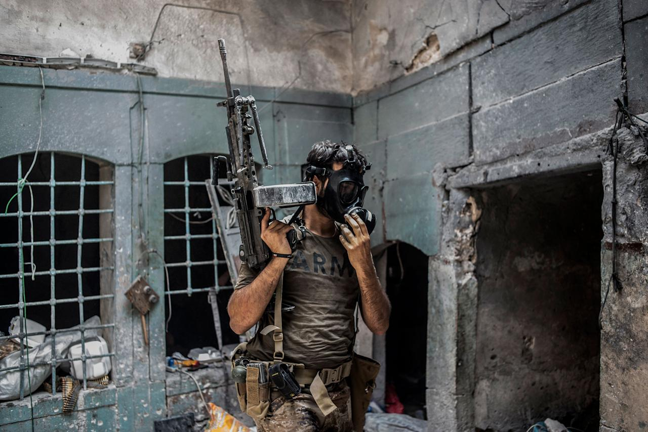 <p>An Iraqi Special Operation Forces (ISOF) soldier wears a gas mask during an Islamic State gas attack in the Islamic State occupied Old City district where heavy fighting continues on July 8, 2017 in Mosul, Iraq. Iraqi forces continue to encounter stiff resistance from Islamic State with improvised explosive devices (IED's), suicide bombers, heavy mortar fire, gas attacks and snipers hampering their advance. (Photo: Martyn Aim/Corbis via Getty Images) </p>