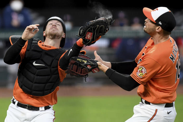 Baltimore Orioles catcher Chance Sisco catches a foul ball from Boston Red Sox's Hunter Renfroe in front of teammate Trey Mancini in the third inning of a baseball game, Saturday, May 8, 2021, in Baltimore. (AP Photo/Will Newton)