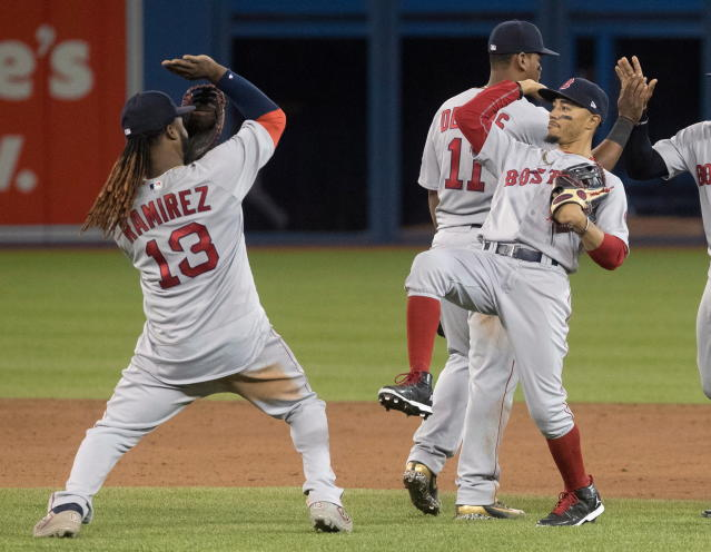 Boston Red Sox's Hanley Ramirez high fives with teammate Mookie Betts celebrate after they defeated the Toronto Blue Jays in a baseball action in Toronto on Wednesday April 25, 2018. (Fred Thornhill/The Canadian Press via AP)