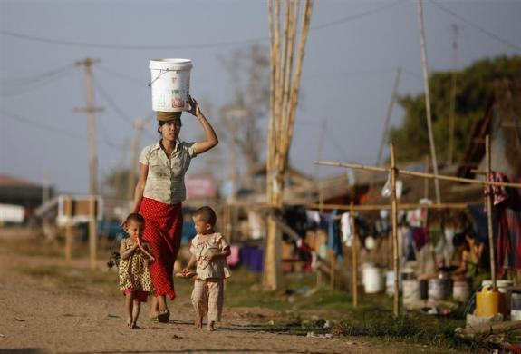 A worker carries a bucket of water as she walks with her children at a temporary residence for construction workers at Naypyitaw, January 26, 2012.