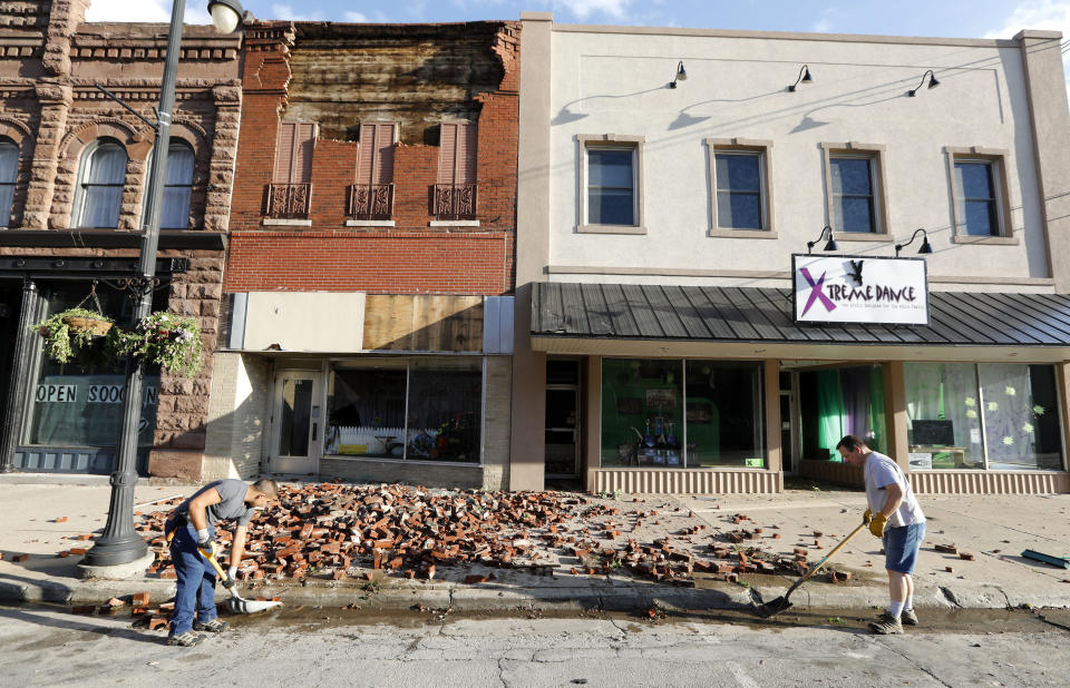 <p>Workers clean up bricks from a tornado-damaged business on Main Street, Thursday, July 19, 2018, in Marshalltown, Iowa. Several buildings were damaged by a tornado in the main business district in town including the historic courthouse. (Photo: Charlie Neibergall/AP) </p>